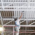 industrial painting contractor spray painting a metal ceiling