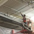 industrial painter spray painting a metal deck ceiling